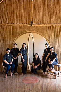 Group in Black Uniform Gathered Around Circular Door in Bali.