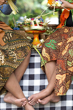 Two women in floral skirts sitting on blanketed bench in Bali.