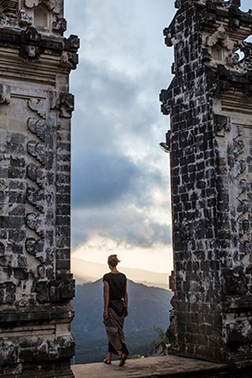 Woman standing between stone archway in Bali.