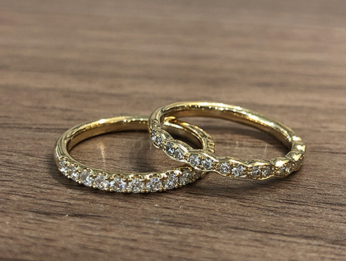 Two Gold Diamond Bands Lying on Table